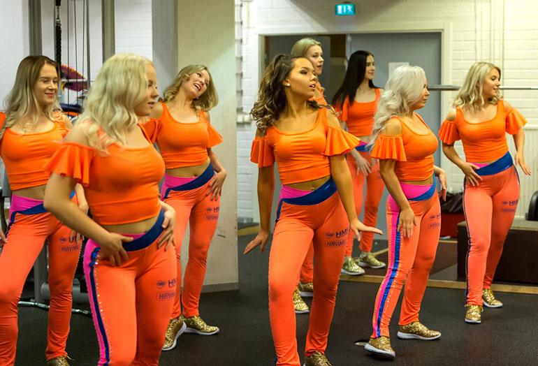 Cheerleaderit kuivaharjoittelevat tanssiliikkeensä kuntosalilla ennen varsinaisen ottelun alkamista.