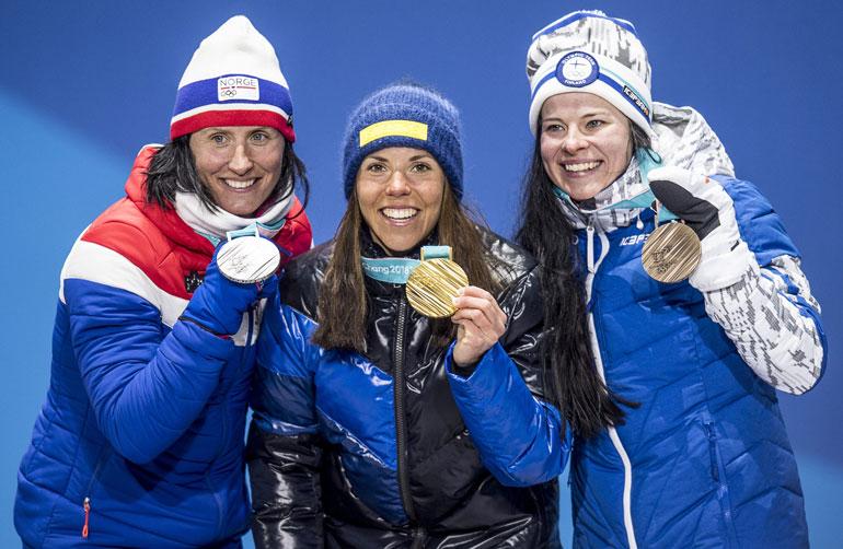 Krista Pärmäkoski (oik.) paineli pronssille. Rinnalla olympiahopeaa saavuttanut Marit Björgen (vas.) sekä olympiavoittaja Charlotte Kalla.