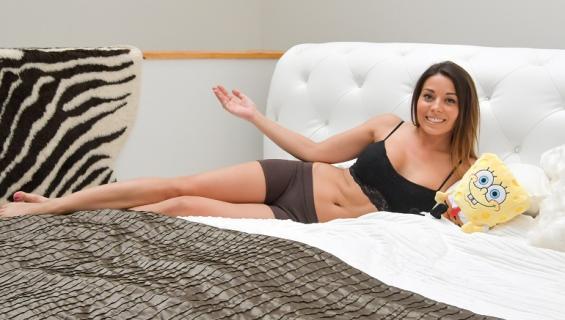 Amanda Harkimo makaa sängyllä.